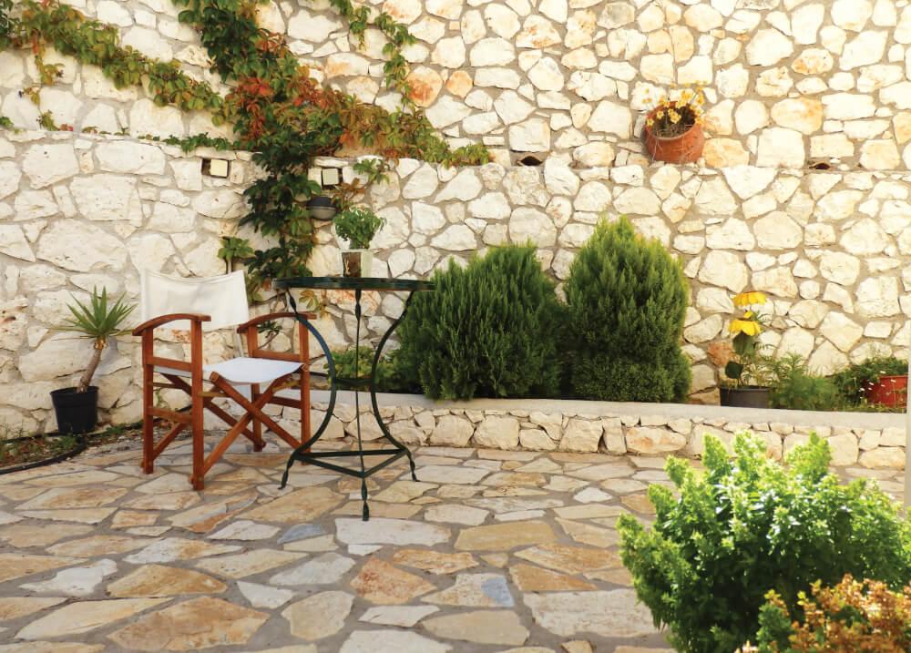 Πέτρινος πλακόστρωτος κήπος με τραπεζάκι και καρέκλα σκηνοθέτη στη Natura Villas Λευκάδας