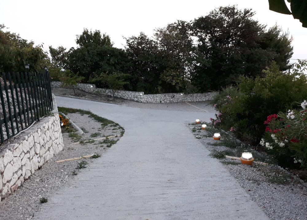 Φωτισμένο ιδιωτικό δρομάκι που οδηγεί στις βίλλες Natura Villas