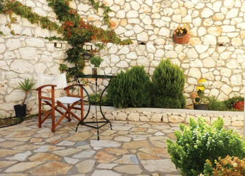Stone paved garden with coffee table and director chair at Natura Villas, Lefkada